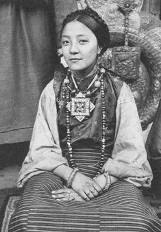 A Tibetan woman (1930s) wears a necklace comprised of ancient dZi, banded agates, coral and a large amulet or gau box. Gaus with the 'two intersecting squares' symbolize two crossed dorjes or a double vajra.  The gau might contain a wealth of sacred items that have been blessed by revered Lamas. They might also contain relics, mantras, a small statue or Tsa Tsa. dZi bead blogspot~