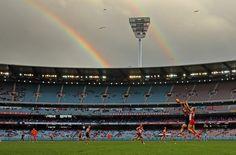 Wettkampf unter Regenbögen: Spieler der Melbourne Demons und Sydney Swans konkurrieren um den Ball.