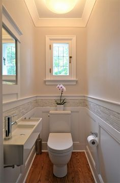 Small Bathroom Secrets: How to Pick the Right Vanity. I like the wall details, only tile between the molding.