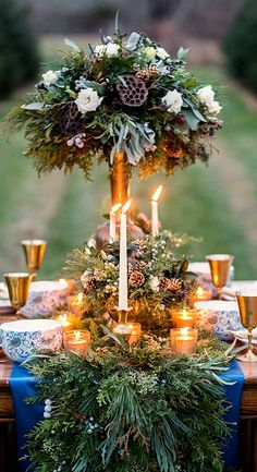 Amber goblets, blue fabric, and seasonal greenery create an unforgettable tablescape.... winter table design