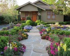 Flower Garden Designs Looks Beautiful Even For Your Front Yard Landcsape : Gorgeous Flower Garden With Colorful Flower Green Plant Stones Walkway Wooden Patio Chairs Wooden Entry Door