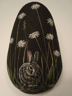 Rabbit and Daisies hand painted on a rock by Ann Kelly.