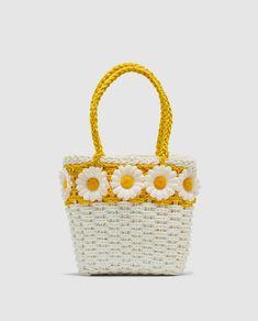 Bolso en color blanco y amarillo, con adorno de flores.