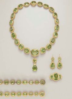 AN ANTIQUE PERIDOT PARURE   Comprising a necklace, suspending a detachable briolette-cut peridot pendant, by a gold foliate cap, to the circular-cut peridot surmount, from a series of oval and cushion-cut peridots, each within a gold beaded frame; a brooch, two bracelets and pair of ear pendants en suite, mounted in gold, circa 1820