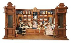 German grocery and novelty shop. Contains a bounty of groceries, teas, a collection of miniature Steins, trays of pastries, scale, rare figural gas lamp, three wooden dolls, and, curiously, hat stands with bonnets as though a milliner's shop. Late-19th century.