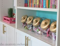 Cookie jars with spray painted lids for organizing for a girl's room. The Creativity Exchange