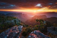 """Sunset from Mariepskop - Evening sunlight blasts through a small gap in the clouds on the horizon, creating an amazing sunset over one of my favourite locations on the planet, the Blyde River Canyon. This view is from Mariepskop, the opposite side of the Three Rondawels that most tourists know.<br></br><br></br>Mariepskop, Mpumulanga, South Africa.<br></br><br></br><a href=""""http://www.markdumbleton.com"""">Website</a> 