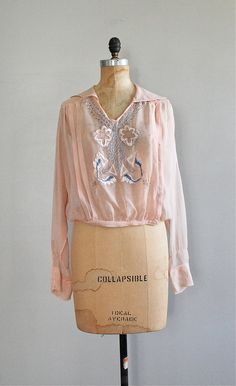 early 1920s very pale pink sheer silk tunic style blouse with intricate blue floral embroidery & tiny metal beads, lace tatting at sleeve cuffs, wide sailor collar, double pintucks from shoulder to waist, snap closure at front waist, snap closures at cuffs and snap closure at left neck.