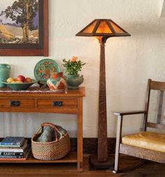 A Royal Craftsman quarter-sawn oak side table in the living room holds ca. 1920s Weller pots and Oaxaca baskets. An oak and mica 'Saugatuck' Mission-style floor lamp from Ragsdale illuminates the space.