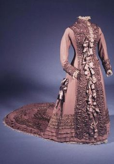 Wedding dress, 1877. Pink-grey fine wool trimmed with ruched satin, satin ribbons and Bedfordshire lace. The all-in-one 'princess gown' has a long fan-shaped train, decorative pockets and trimmings in a combination of fabrics which are all fashionable features of that year.