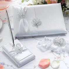 "This Butterfly beauty guest book   is covered in white satin. The 5.25"" pen base holds a silver pen with black ink. Both the pen base and 10"" x 6.5"" guest book cover are wrapped in white satin ribbons and accented by beaded butterfly ornaments. The guest book contains 30 two-sided pages for a total of 580 signatures"