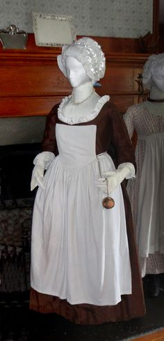 Quaker Round Gown c.1775 Robe a l'anglaise round gown (back cut en fourreau), reproduction of extant dress of Phoebe Massey, c. 1775, at the Massey House., Broomall PA. Like the original, it is made in brown silk with a linen-lined bodice and sleeves; entirely hand-sewn and constructed from a pattern taken directly from the original garment. Mitts, white linen with blue silk embroidery, reproduction of extant item in the costume collection of Colonial Williamsburg (accession #1985-216.1).