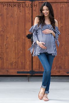 A gingham print maternity top. Open shoulder neckline with ruffle trim. 3/4 sleeves with tie accent. Adjustable cami straps. This style was created to be worn before, during, and after pregnancy. #PregnancyOutfits