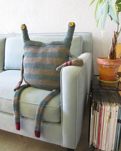 """$195 Beast Pillow No. 164 by Debi Van Zyl. Made to order, hand knitted pillows of cotton & alpaca wool yarn, stuffed w/ polyfil. Measures about 31"""" long x 13"""" wide. Recycled buttons for eyes, arms & legs are unstuffed, looks like stripes are knitted as part of the beast but the mouth is probably duplicate stitch in same yarn as the stripes. Beasts are pillows but not a pillow cover."""