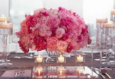 Beautiful centerpiece idea: Using flowers of different shades of 1 color and multi-level candles (votive candles and floating candles in high glass stands).