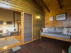 The covered deck with comfortable couch at Cliffhanger Cottage.