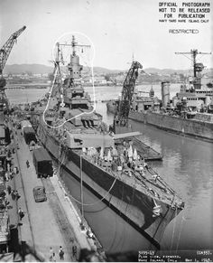 "USS Indianapolis from starboard bow, at Mare Island Navy Yard, California, following overhaul, 1 May 1943. White outlines mark recent alterations. Note new forward superstructure, 8""/55 triple gun turrets, starboard anchor, anchor gear on forecastle, & paravane downrigging chains at extreme bow. USS Minneapolis (CA-36) in background stripped for overhaul."