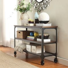 The Merida Mixed Media Console features a lower shelf and 4 wheels for easy, convenient transportation. The rustic industrial design of this must-have piece includes black sanded metal supports and a hardwood top for a laid-back look. This piece's portability makes it an ideal friend in the kitchen, office or even as a bar cart in the dining room.