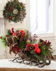 Petit traîneau décoré avec boules de Noël et pommes de pin