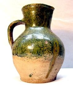 Pottery small round jug; Tudor Green Ware; buff fabric with yellow-green glazed upper; lipped, flat rim, tall neck & squat ovoid body with f... 7.4in tall