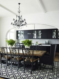 Chic black and white open plan dining room with black crystal chandelier over black trestle based dining table with salvaged wood top paired with black chippendale chairs and black wingback captain chairs over black and white geometric rug. Elegant Dining Room, Dining Room Design, Dining Room Furniture, Dining Rooms, Dining Tables, Painted Dining Chairs, Dinning Chairs, Wood Tables, Room Chairs