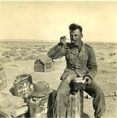 """War in the Western Desert, 1941-43: Trooper of the AfrikaCorps at chow time. A jerrycan serves as stool. The food was very basic, often some kind of soup or stew prepared with """"long-life"""" ingredients. Note the pith helmet sitting next to the trooper."""