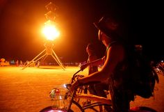 Participants watch the flames on the Spire of Fire installation on Aug. 29.