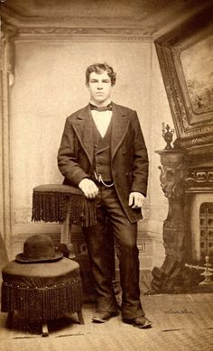 Carte de visite of unknown young man with bowler hat on stool, standing in front of fireplace backdrop, ca 1868.  Collection David Claudon, 2011