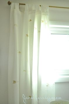 spray painted gold curtain rod from Target and hand stamped curtains with gold arrows
