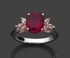 BAGUE RUBIS  Elle est ornée d'un rubis ovale dans un entourage de diamants roses taille navette. Monture en ors 18K.  Poids brut : 6,5 gr.  Poids du rubis : 2,84 carats.  Poids des diamants roses : 0,35 carat environ.  TDD : 54  Le rubis est accompagné d'un rapport du Laboratoire Gübelin énonçant selon son opinion : origine Birmanie, sans trace de traitement thermique.  Estimation 80.000/100.000€