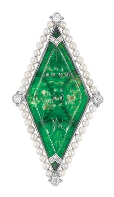 Art Deco Platinum, Carved Jade, Seed Pearl and Diamond Brooch, Yard  Centering one lozenge-shaped carved jade depicting a floral motif, approximately 18.7 x 41.0 x .8 mm., tipped by two curved platinum bands set with 6 rose-cut diamonds, edged by seed pearls approximately 2.3 mm., quartered by 4 old European-cut diamonds, signed Yard, circa 1920.