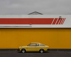 An old yellow car in front of a yellow wall.