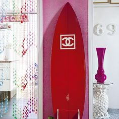 Using sports equipment to create a display, or other items relating to a much-loved hobby, gives a hallway a personlised feel. The pink wallpaper enhances the vibrant colour of the surfboard.