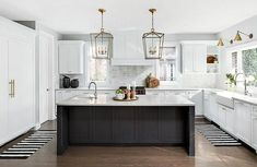 Well appointed black and white kitchen boasts a black center island topped with a white quartz countertop holding a curved prep sink with a polished nickel gooseneck faucet beneath Darlana Lanterns.