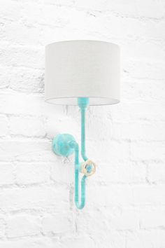 Designer turquoise sconce with creative dimmer and grey linen shade on white brick wall in urban loft interior. Industrial spirit in new, colorful and extraordinary incarnation. Available in Zapalgo online store.