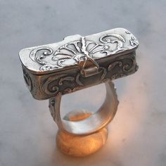 Lora Hart -- Finally finished a ring I started in a class with Louise Duhamel and Gordon Uyehara. Taken not taught of course.  Slip printed, metal clay hinges, dry constructed. Broken and repaired three times. I think the scar adds some personality, don't you?