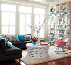 In this family room, the white coffee table, rug, and bookshelf wall unify the room, while a dark sectional frames one end of the space. Then, a few colorful accent pieces, such as pillows and decorative accessories on the shelves, add personality. Blue, with an occasional pop of pink, is repeated for consistency.