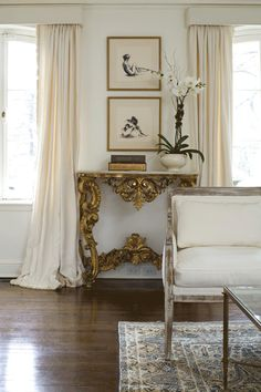 White curtains puddled on a dark wood floor.  Gilt console with charcoal drawings. Dreamy!