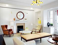 Painting the formerly drab living room white set off the early-to mid-20th-century furnishings, including a low table, wall light and Visiteur chair, right, by Jean Prouvé | archdigest.com