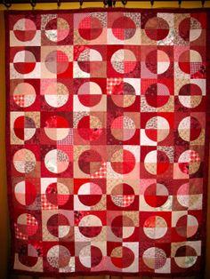 Talin's corner - great Drunkard's Path blocks set into circles / study in red fabrics.