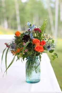 Wildflower arrangement in ball jar by Mountain Flowers of Aspen with roses, thistle, and safflower. #aspen #wedding #wildflowers