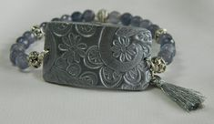 Stretch bracelet with rectangular polymer charm, silver tassel and dyed jade grey/gray beads