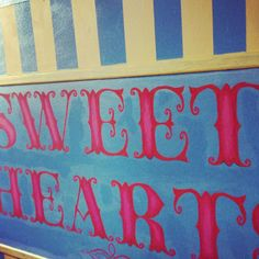 """We have a traditional sweet shop inspired candy bar. It is blue and yellow striped with chalk boards on three sides allowing you to add a personal note or menu; on the forth side it has 'Sweet Hearts"""" in pink hand painted in a Willy Wonka style font. It also has a matching canopy mounted on 4 spindles we reclaimed for a school in Bude. This can be used as a candy bar, a fete stall or for whatever you like. Hire this for £100"""