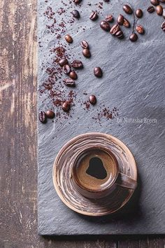 For Coffee Lovers - Brown ceramic cup of coffee and coffee beans over black slate as background. With copy space at right. Top view. #CupOfCoffee