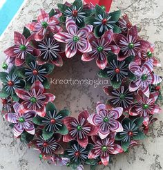 Origami paper flower wreath Put a little jingle on your door, wall or table.....This beautiful Origami Flower Christmas Wreath would be a stand out in your home!! This would also be the perfect gift for that someone special! The possibilities are endless! This wreath has 3 rows of 30+ Christmas flowers made from scrapbook paper that are cut into 3x3 then folded into a petal to be combined to makes a beautiful flower. The span of the flower is approx 3. They are hand glued to a base and the…