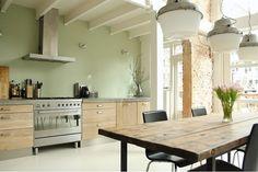 Houten keuken met stoere details en zachtgroene muur.