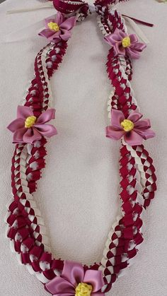 The lei is approximately 36 inches long material/ 3/16 and 3/8 satin ribbon Color ★ beige and burgundy with marve color flower ★ light yellow and navy with royal blue color lower