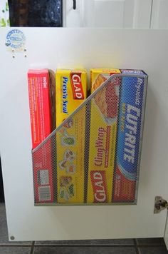 Kitchen cupboard organisation --- using a magazine holder to store your boxes of tin-foil, cling film, baking parchment etc. -- Only will work if the shelf inside the cupboard is set back a couple of inches.