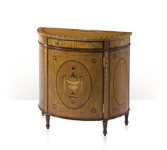 A fine satinwood, rosewood banded and sycamore marquetry inlaid demi lune side cabinet, the finely leaf and fan inlaid top above an anthemion and honeysuckle inlaid frieze with a drawer, above a classical yew burl inlaid urn and oval walnut banded cabinet door and side panels, enclosing an adjustable shelf, on turned and inlaid tapering legs.