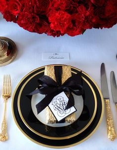Glam table setting in black and gold with a stunning centerpiece of red! #tablescape #blackandgold #placesettings
